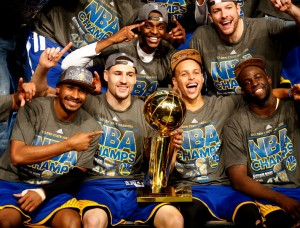 """The Golden State Warriors, including Golden State Warriors' Klay Thompson (11) and Golden State Warriors' Stephen Curry (30) celebrates with the NBA championship trophy after the Golden State Warriors 105-97 win over the Cleveland Cavaliers in Game 6 of the NBA Finals to win the NBA Championship at Quicken Loans Arena in Cleveland, Ohio, on Tuesday, June 16, 2015. (Nhat V. Meyer/Bay Area News Group)"""